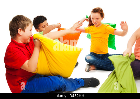 Happy three teen kids, boys and girls ready to start fighting with pillows, laughing and having fun, isolated on - Stock Photo