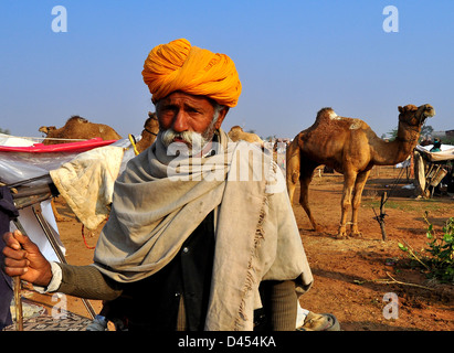 A Farmer stands with his camel at nagaur Cattle Fair in western Indian Rajasthan state. - Stock Photo