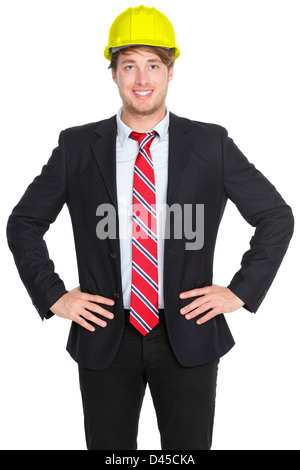 Portrait of confident young male engineer or architect in suit wearing helmet isolated on white background - Stock Photo