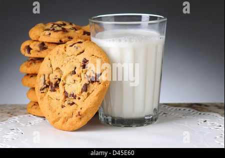 Stack of chocolate chip cookies next to a glass of milk. Horizontal format on a light to dark background. - Stock Photo