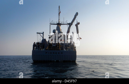 USS Pioneer recovers an airborne mine countermeasure device. - Stock Photo