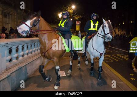 Police horses and riders in full riot gear advancing down Whitehall at night, Day X3 Student Demonstration, London, - Stock Photo