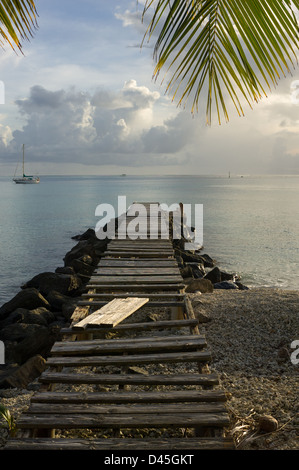 Ramshackle jetty leading from the beach near Fare, Huahine, French Polynesia - Stock Photo