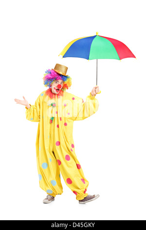 Full length portrait of a cheerful clown holding a colorful umbrella isolated on white background - Stock Photo