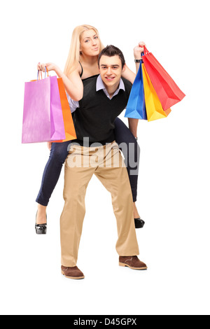 Full length portrait of a young man giving a piggyback ride to a woman with shopping bags isolated on white background - Stock Photo