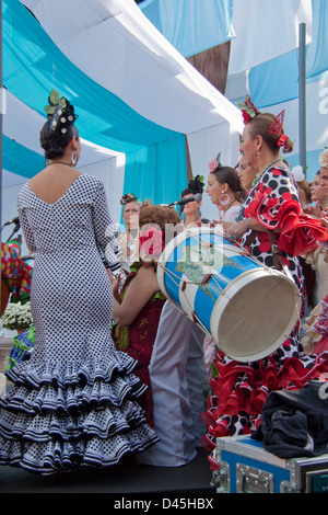 Women's chorus  wearing  traditional flamenco style dresses in a fair in Andalusia. - Stock Photo