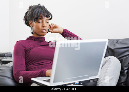 Black Woman with serious expession while using laptop - Stock Photo