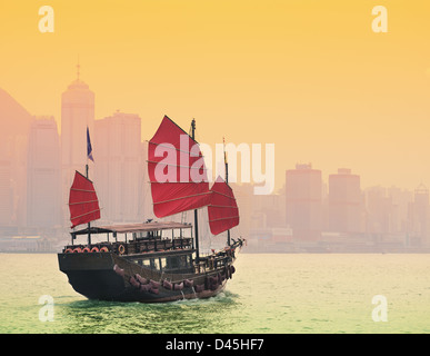 A traditional Junk sailing in Victoria Harbor in Hong Kong. - Stock Photo