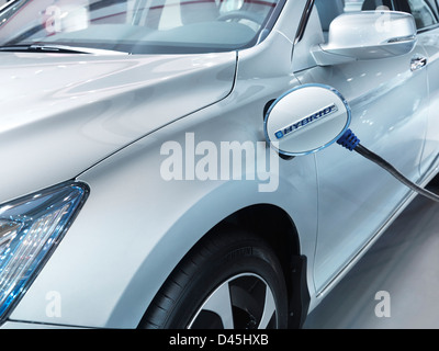 Plug-in hybrid electric vehicle recharging batteries at a charging station. Closeup of car power socket lid. 2014 - Stock Photo