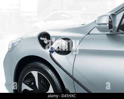 Plug-in electric car with a power cord plugged into a power socket, recharging batteries at a charging station - Stock Photo