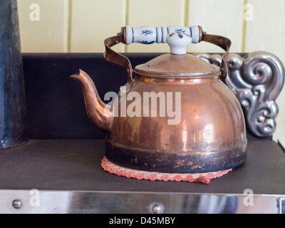 Copper Kettle. An old antique kettle on an old stove. - Stock Photo