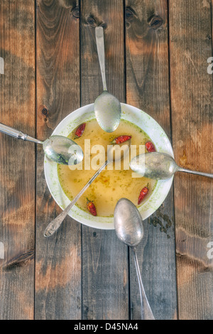 soup plate with hot chillies and five spoons - Stock Photo