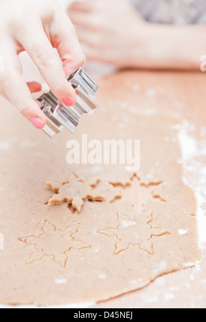 Closeup of hand of young girl making star shaped gingerbread biscuits with metal cutter from dough - Stock Photo