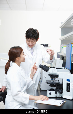 a female and male doctor with a microscope - Stock Photo