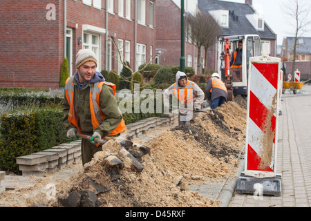 Hungarian migrant workers do earth work for the construction of a glass fiber infrastructure in Netherlands - Stock Photo