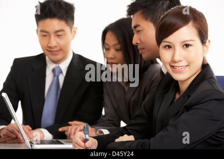 Studio Shot Of Chinese Businesspeople Having Meeting - Stock Photo