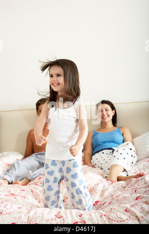 Family Bouncing On Bed Together - Stock Photo
