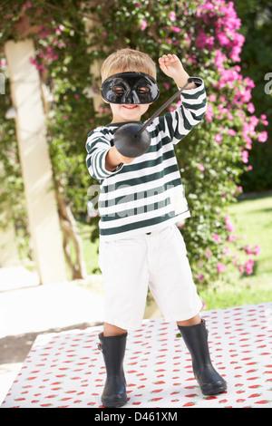 Young Boy Wearing Wellington Boots Drinking Milkshake - Stock Photo
