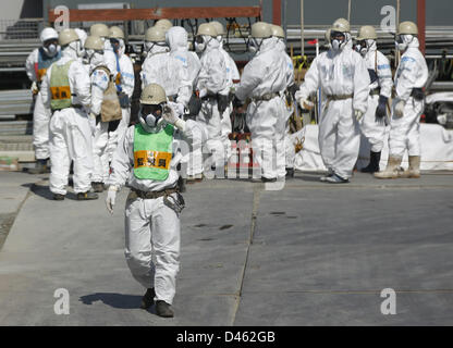 Fukushima, Japan. 6th March 2013. Workers wearing protective suits and masks are seen next to the No.4 reactor at - Stock Photo
