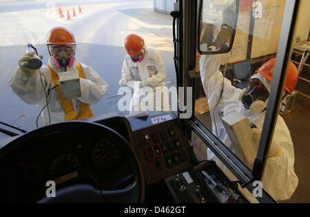 Fukushima, Japan. 6th March 2013. Workers carry out radiation screening on a bus for a media tour at Tokyo Electric - Stock Photo
