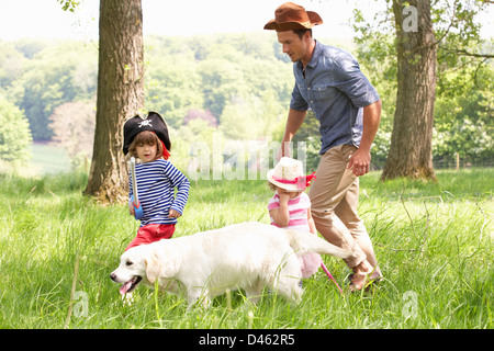 Father Playing Exciting Adventure Game With Children And Dog In Summer Field - Stock Photo