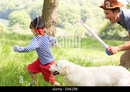 Father Playing Exciting Adventure Game With Son And Dog In Summer Field - Stock Photo