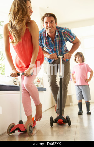 Parents Riding Childrens Scooters Whilst Son Looks On - Stock Photo