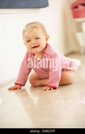 Unhappy Baby Girl Sitting On Floor Crying - Stock Photo