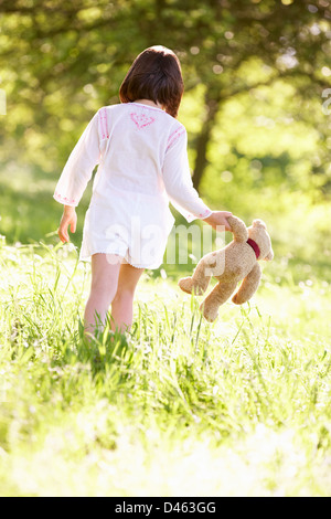Young Girl Walking Through Summer Field Carrying Teddy Bear - Stock Photo