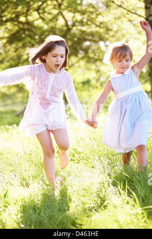 2 Young Girls Walking Through Summer Field Together - Stock Photo
