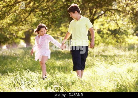 Boy And Girl Walking Through Summer Field Together - Stock Photo