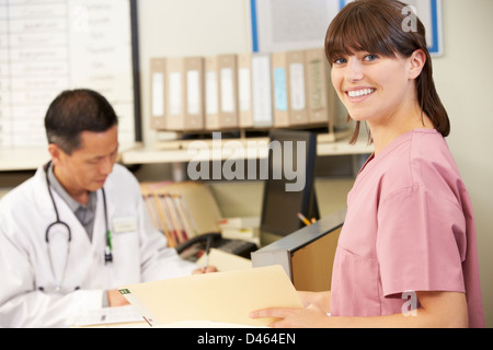 Nurse With Doctor Working At Nurses Station - Stock Photo