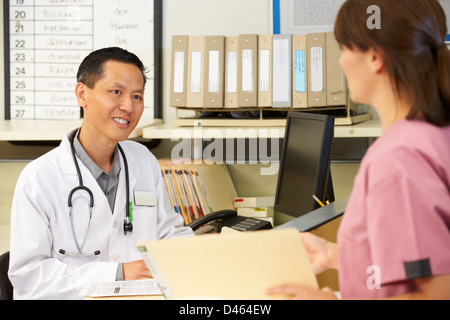 Nurse With Doctor Working At Nurses Station Stock Photo