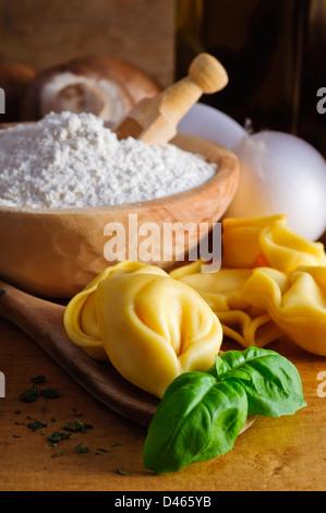 Traditional homemade italian pasta tortellini and ingredients - Stock Photo