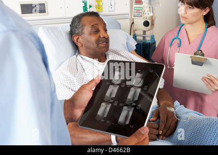 Doctor Using Digital Tablet In Consultation With Senior Patient - Stock Photo