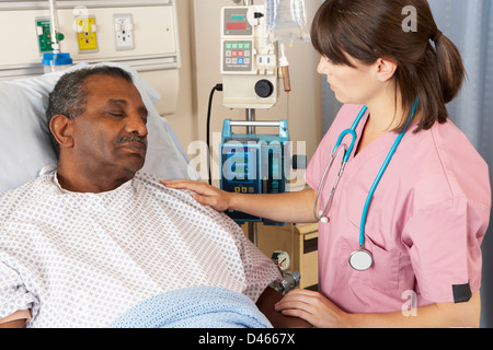 Nurse Checking Senior Male Patient On Ward - Stock Photo