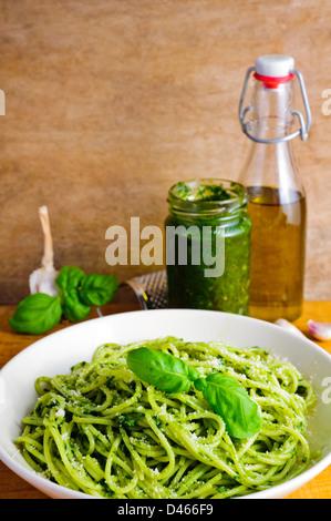 Traditional homemade italian spaghetti pasta and basil pesto ingredients - Stock Photo
