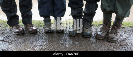 Walkers show off their muddy boots on a footpath. - Stock Photo