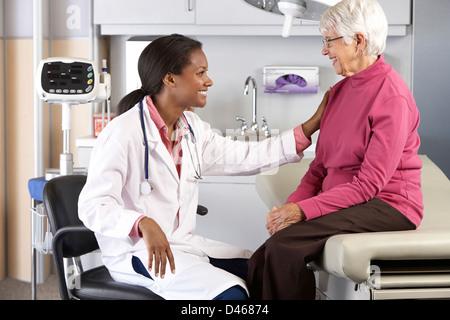 Doctor Examining Senior Female Patient - Stock Photo