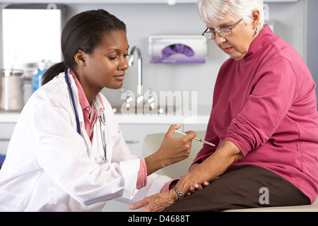 Doctor Giving Senior Female Patient Injection - Stock Photo