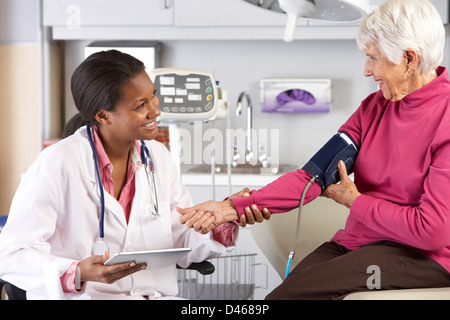 Doctor Taking Senior Female Patient's Blood Pressure - Stock Photo