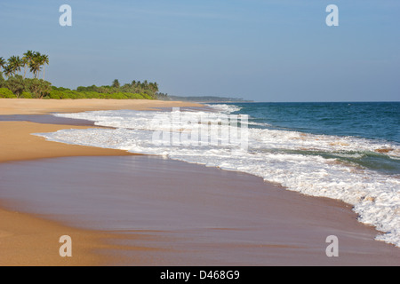 WAVES BREAKING INTO FOAM AND SURF ON A TROPICAL BEACH - Stock Photo