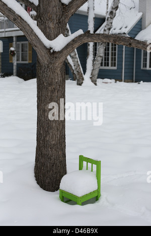 A child's wooden chair in the snow. - Stock Photo