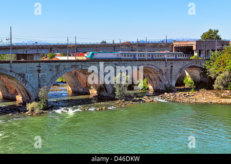 Train passes on stone railway bridge over the river with green water in Moncalieri in Piedmont, Northern Italy. - Stock Photo