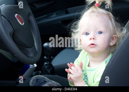 Baby girl sitting on the driver's seat in a family car. - Stock Photo