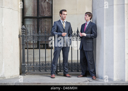 two wall street suits having a cigarette break - Stock Photo