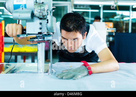 worker using a cutter - a large machine for cutting fabrics- in a Chinese textile factory, he wears a chain glove - Stock Photo