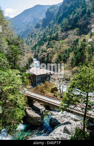 Steep valley with stream, bridge and buildings in the rural heartland of Central Japan. - Stock Photo