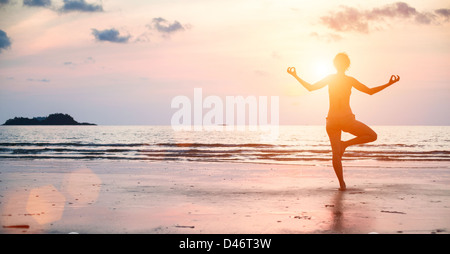 Yoga woman performs an exercise on the beach during sunset. - Stock Photo