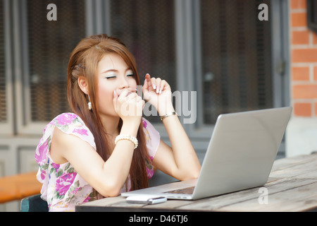 Young attractive business woman working on her laptop at outdoors cafe, She look very yawning. - Stock Photo